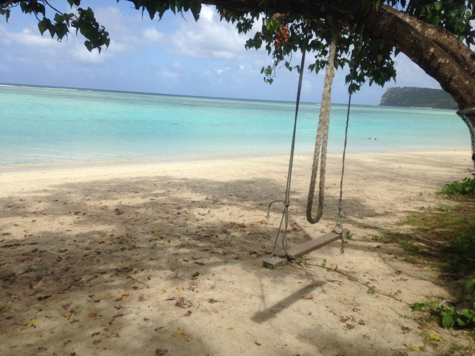 A rope swing in front of blue ocean water at the beach in Guam